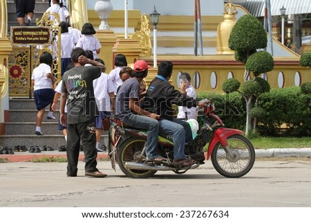 KANCHANABURI, THAILAND - SEPTEMBER 4: Local school children at the Wat Chai Chumphon Chana Songkhram with a motor bike  in foreground in the town of Kanchanaburi, Thailand on the 4th September, 2014.