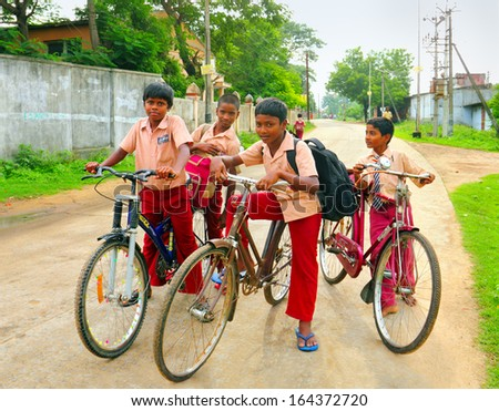 KANCHI, INDIA - AUG 16: Unidentified hindu school children dressed in uniform go home after classes by their bicycles on August 16, 2013 in Kanchipuram, Tamil Nadu, Southern India - stock photo