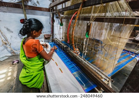 KANCHIPURAM, INDIA - SEPTEMBER 12, 2009: Woman weaving silk sari on loom. Kanchipuram is famous for hand woven silk sarees and most of the city's workforce is involved in  weaving industry - stock photo