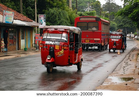 KANDY, SRI LANKA - DECEMBER 6, 2008: Red vehicles in the street in the North of Sri Lanka on a rainy day. At this very time the Government troops attacked Tamil militants in the North of the country.  - stock photo