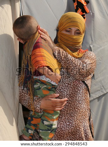 KANKE REFUGEE CAMP, DOHUK, KURDISTAN, IRAQ - 2015 JULY 4  - A Yazidi mother and her child who escaped abuse from ISIS outside her tent in Kanke refugee camp