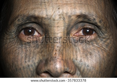 KANPETLET MYANMAR, DECEMBER 9: Chin tribe tattoed woman (Yin Duu) poses for a photo on December 9, 2015 Kanpetlet, Myanmar. Also known as the Kakis they are a number of Tibeto-Burman tribal people. - stock photo