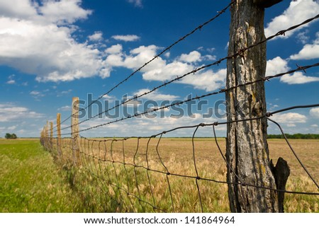 Kansas pastureland; fence with barbed wire - stock photo