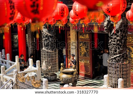 KAOHSIUNG CITY, TAIWAN - JAN 18, 2015: Unidentified prayer holding incense sticks pray at old traditional Sanfeng Temple, which is one of the oldest temples in Kaohsiung, dating back 300 years.  - stock photo