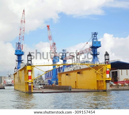 KAOHSIUNG, TAIWAN -- AUGUST 12, 2015: A floating dry dock is surrounded by construction cranes in the wharf area of Kaohsiung Port.