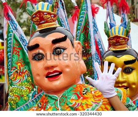 KAOHSIUNG, TAIWAN -- AUGUST 15, 2015: Two dancers in modernized costumes of the Chinese Third Prince tradition pose at a local temple carnival. - stock photo