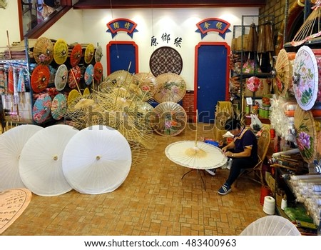 KAOHSIUNG, TAIWAN -- JULY 24, 2016: A female craftsperson makes oil-paper umbrellas, which is a traditional art and craft product by the Chinese Hakka people.