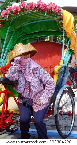 KAOHSIUNG, TAIWAN -- JULY 25, 2015: A female cycle rickshaw driver, wearing a traditional Hakka style strawhat, waits for new customers.  - stock photo