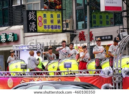 KAOHSIUNG, TAIWAN -- JULY 9, 2016: A percussion ensemble plays large ceremonial drums on the back of a truck during a traditional temple procession.