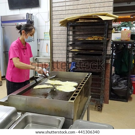 KAOHSIUNG, TAIWAN -- JUNE 9, 2016: A female chef at a traditional Chinese breakfast shop prepares fried pancakes with egg and scallions.