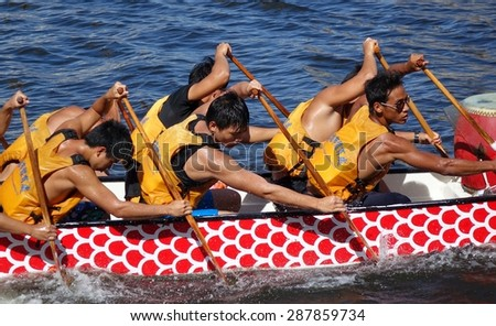 KAOHSIUNG, TAIWAN - JUNE 14, 2015: An unidentified team of rowers trains for the upcoming Dragon Boat Races on the Love River. - stock photo