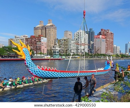 KAOHSIUNG, TAIWAN -- MAY 27, 2016: A crane lowers a dragon boat into the Love River in preparation for the upcoming Dragon Boat Festival.