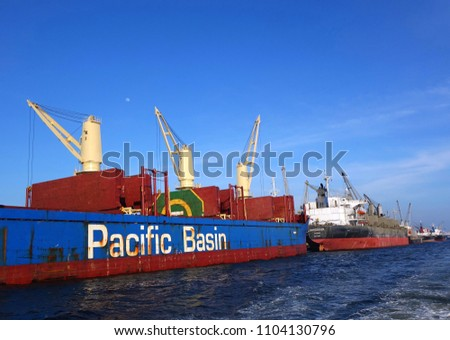 KAOHSIUNG, TAIWAN -- MAY 26, 2018: A large ocean-going cargo ship with cranes in the busy port of Kaohsiung, a major trading hub for Taiwan.