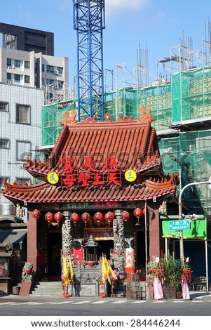 KAOHSIUNG, TAIWAN -- MAY 15, 2015: Old and New -- New building construction towers over the traditional Tsi Tian Temple in Kaohsiung City. - stock photo