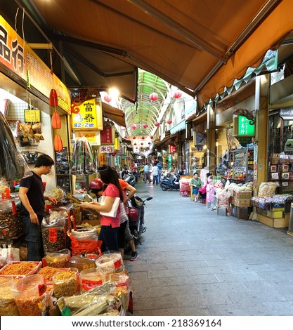 KAOHSIUNG, TAIWAN -- MAY 31, 2014: Shoppers buy goods at the famous Zongjie dry goods market which sells grains, nuts, dried meat, fish, seafood, herbs and fruits. - stock photo