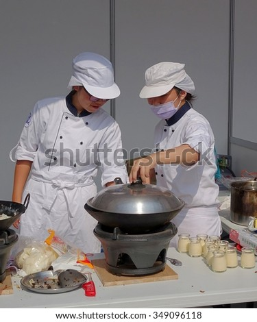 KAOHSIUNG, TAIWAN -- NOVEMBER 28, 2015: Two chefs prepare a steamer for the cooking competition during the 2015 Hakka Food Festival, which is a yearly public outdoor event.