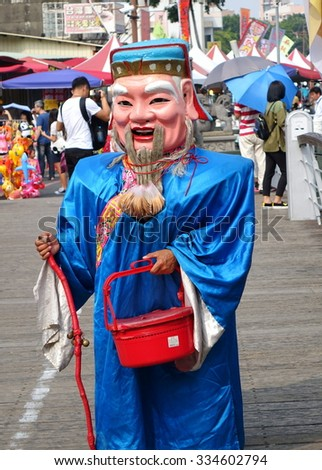 KAOHSIUNG, TAIWAN -- OCTOBER 17, 2015: A man dressed up as the traditional Chinese God of Wealth begs for lucky charm donations. - stock photo