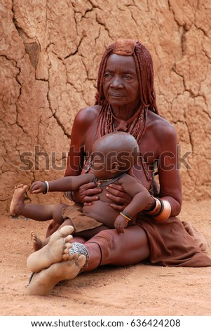 KAOKOVELD, NAMIBIA - OCT 13, 2016: Unidentified Himba woman with her grandchild in front of the hut. She takes care of the child. The himbas are a traditional tribe in Africa.