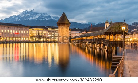 Kapellbrucke Chapel Bridge and Water Tower under Dramatic Sky Illuminated Building Reflection from Reuss River Sceneic Night Panorama Cityscape Skyline. Covered bridge in Lucerne, Switzerland
