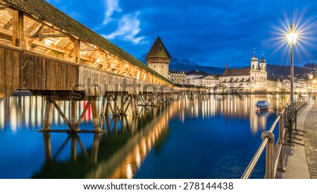 Kapellbrucke Panorama night view Historic Chapel bridge (Famous covered wooden footbridge), Water Tower and Jesuitenkirche over Reuss river Cityscape old town under Dramatic Blue Sky, Switzerland - stock photo