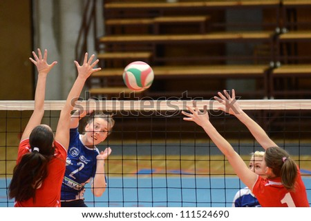 KAPOSVAR, HUNGARY - APRIL 22: Zsanett Pinter (blue 2) in action at the Hungarian I. League volleyball game Kaposvar (blue) vs Budai XI. SE (red), April 22, 2012 in Kaposvar, Hungary. - stock photo