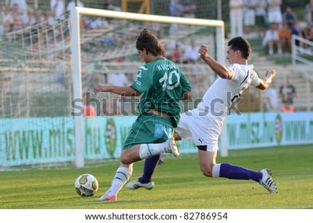 KAPOSVAR, HUNGARY - AUGUST 14: Kornel Kulcsar (in green) in action at a Hungarian National Championship soccer game - Kaposvar (green) vs Ujpest (white) on August 14, 2011 in Kaposvar, Hungary. - stock photo