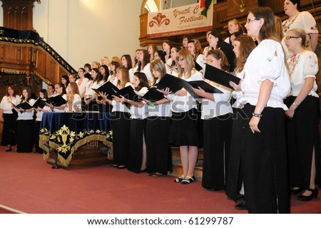 KAPOSVAR, HUNGARY - AUGUST 26: Members of the Kodaly Zoltan Grammar School Choir sing at the IV. Pannonia Cantat Youth Choir Festival August 26, 2010 in Kaposvar, Hungary - stock photo