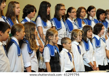 KAPOSVAR, HUNGARY - AUGUST 26: Members of the Marianum Komarno Choir sing at the IV. Pannonia Cantat Youth Choir Festival August 26, 2010 in Kaposvar, Hungary - stock photo