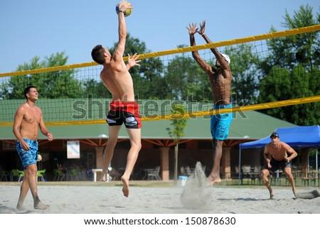 KAPOSVAR, HUNGARY - AUGUST 4: Tamas Kaszap (with ball) in action at a ROAK Viragfurdo Kupa beach volleyball competition, August 4, 2013 in Kaposvar, Hungary. - stock photo