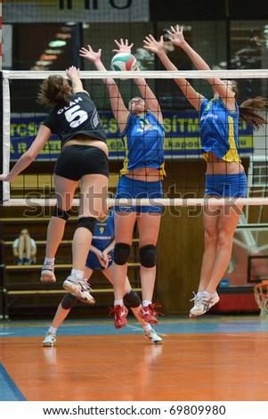 KAPOSVAR, HUNGARY - JANUARY 23: Marianna Palfy (C) blocks the ball at the Hungarian NB I. League woman volleyball game Kaposvar vs Miskolc, January 23, 2011 in Kaposvar, Hungary. - stock photo