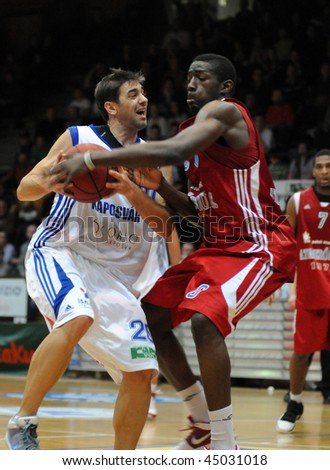 KAPOSVAR, HUNGARY - JANUARY 20: Matija Ceskovic (in white) in action at Hungarian National Championship basketball game with Kaposvar vs Paks on January 20, 2010 in Kaposvar, Hungary.