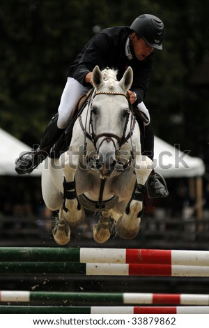 KAPOSVAR, HUNGARY - JULY 18: An unidentified competitor jumps with his horse on Hungarian Jumping Championship Final for adult riders, July 18, 2009 in Kaposvar, Hungary - stock photo