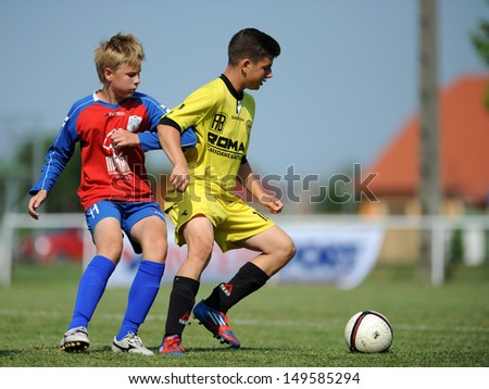 KAPOSVAR, HUNGARY - JULY 20: Unidentified players in action at the IX. Youth Football Festival match Minsk (red) (BLR) vs. Brasov (yellow) (ROM) on July 20, 2013 in Kaposvar, Hungary - stock photo