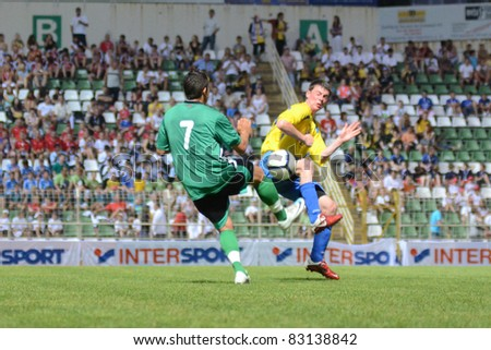KAPOSVAR, HUNGARY - JULY 18: Unidentified players in action at the VII. Youth Football Festival under 16 match SYFA West R (yellow)(SCO) vs. Rakoczi FC (green) (HUN) on July 18, 2011 in Nagyberki, Hungary
