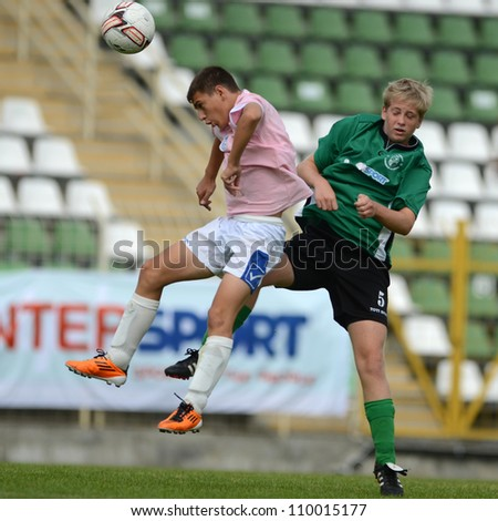 KAPOSVAR, HUNGARY - JULY 21: Unidentified players in action at the VIII. Youth Football Festival U14 match Tirgu Mures (pink) (ROM) vs. Kaposvar (green)(HUN) on July 21, 2012 in Kaposvar, Hungary