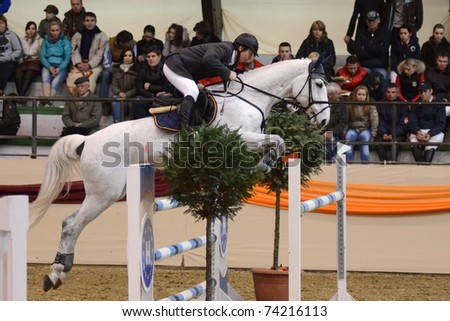 KAPOSVAR, HUNGARY - MARCH 27: Akos Kajtar jumps with his horse (Ocskas) on the Masters Tournament International Jumping Competition, March 27, 2011 in Kaposvar, Hungary - stock photo