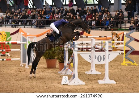 KAPOSVAR, HUNGARY - MARCH 15: Alexandra Vindeczker jumps with his horse (Calli Top) on the Masters Tournament International Jumping Competition, March 15, 2015 in Kaposvar, Hungary - stock photo