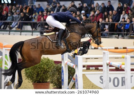 KAPOSVAR, HUNGARY - MARCH 15: Andras Marton jumps with his horse (Fortender) on the Masters Tournament International Jumping Competition, March 15, 2015 in Kaposvar, Hungary - stock photo