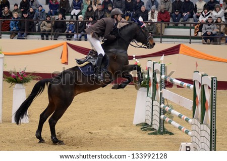 KAPOSVAR, HUNGARY - MARCH 24: Andras Zajzon jumps with his horse (Conrad) on the Masters Tournament International Jumping Competition, March 24, 2013 in Kaposvar, Hungary - stock photo