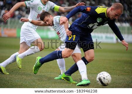 KAPOSVAR, HUNGARY - MARCH 16: Gergo Vaszicsku (blue 91) in action at a Hungarian Championship soccer game - Kaposvar (white) vs Puskas Akademia (blue) on March 16, 2014 in Kaposvar, Hungary. - stock photo