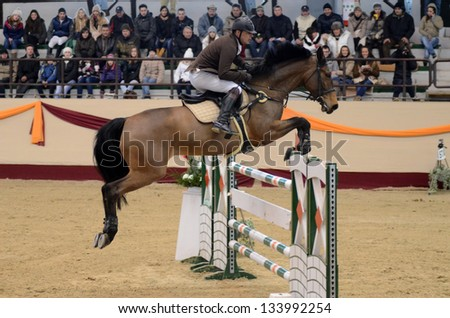 KAPOSVAR, HUNGARY - MARCH 24: Jozsef Pirik jumps with his horse (Starlet) on the Masters Tournament International Jumping Competition, March 24, 2013 in Kaposvar, Hungary - stock photo