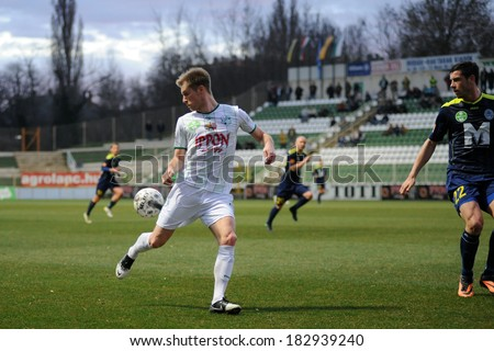 KAPOSVAR, HUNGARY - MARCH 16, 2014: Kink Tarmo (with ball) in action at a Hungarian Championship soccer game - Kaposvar (white) vs Puskas Akademia (blue). - stock photo