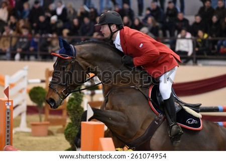 KAPOSVAR, HUNGARY - MARCH 15: Laszlo Kiss jumps with his horse (Salute) on the Masters Tournament International Jumping Competition, March 15, 2015 in Kaposvar, Hungary - stock photo