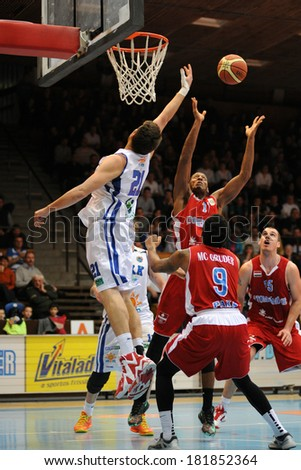 KAPOSVAR, HUNGARY - MARCH 8: Marton Horvath (white 21) in action at a Hungarian Championship basketball game with Kaposvar (white) vs. Paks (red) on March 8, 2014 in Kaposvar, Hungary. - stock photo
