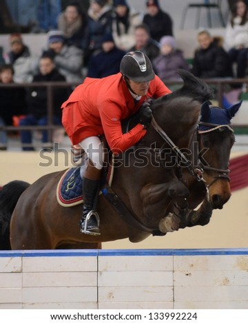 KAPOSVAR, HUNGARY - MARCH 24: Szabolcs Krucso jumps with his horse (Chacco Boy) on the Masters Tournament International Jumping Competition, March 24, 2013 in Kaposvar, Hungary - stock photo