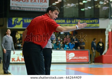 KAPOSVAR, HUNGARY - NOVEMBER 27: Balazs Sabali (Kormend trainer) (in red) in action at a Hungarian Championship basketball game Kaposvar vs. Kormend November 27, 2010 in Kaposvar, Hungary.