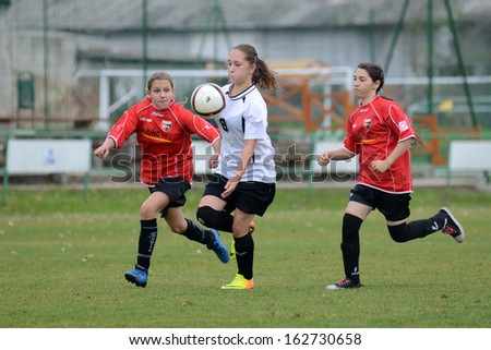 KAPOSVAR, HUNGARY - NOVEMBER 3: Csenge Ujvari (white 8) in action at Hungarian Championship under 15 women soccer game Rakoczi FC (white) vs Pecsi MFC (red) November 3, 2013 in Kaposvar, Hungary. - stock photo
