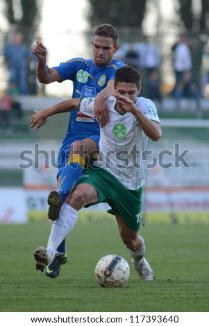 KAPOSVAR, HUNGARY - OCTOBER 20: Drazen Okuka (in white) in action at a Hungarian National Championship soccer game - Kaposvar (white) vs Siofok (blue) on October 20, 2012 in Kaposvar, Hungary.