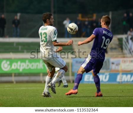 KAPOSVAR, HUNGARY - SEPTEMBER 14: Drazen Okuka (in white) in action at a Hungarian Championship soccer game - Kaposvar (white) vs Ujpest (purple) on September 14, 2012 in Kaposvar, Hungary. - stock photo