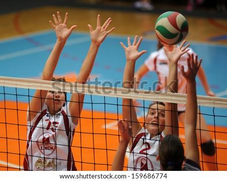 KAPOSVAR, HUNGARY - SEPTEMBER 20: Krisztina Stirt (white 15) in action at the Hungarian I. League volleyball game Kaposvar (white) vs Ujpest (purple), September 20, 2013 in Kaposvar, Hungary. - stock photo
